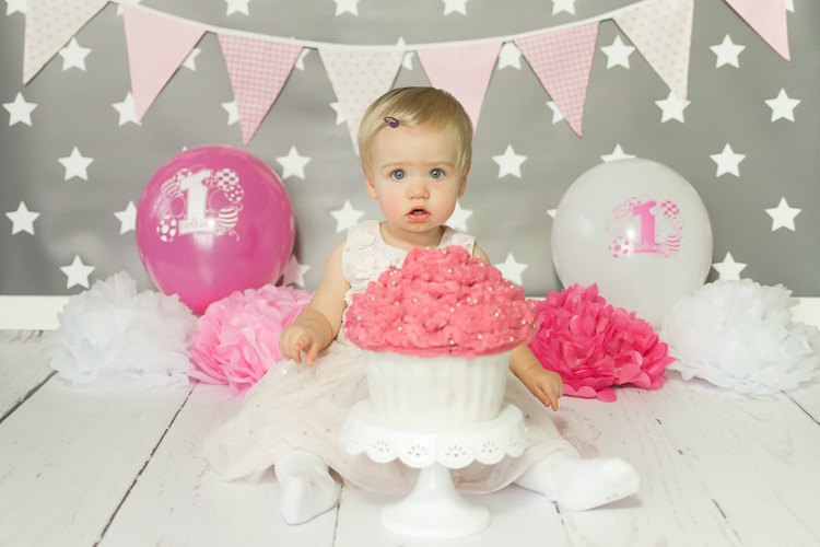 Kleines Mädchen sitzt vor einen großen Cupcake mit rosafarbener Buttercreme, rosa und weiße Ballons im Hintergund. Cakesmash Erkrath von Ella Photography