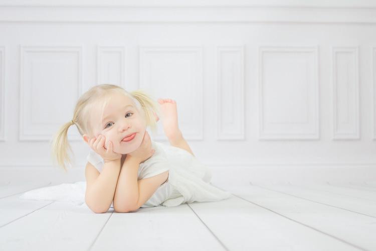 Kleines Mädchen liegt auf einem weißen Holzboden und streckt die Zunge raus. Kinderfotos Erkrath von Ella Faust