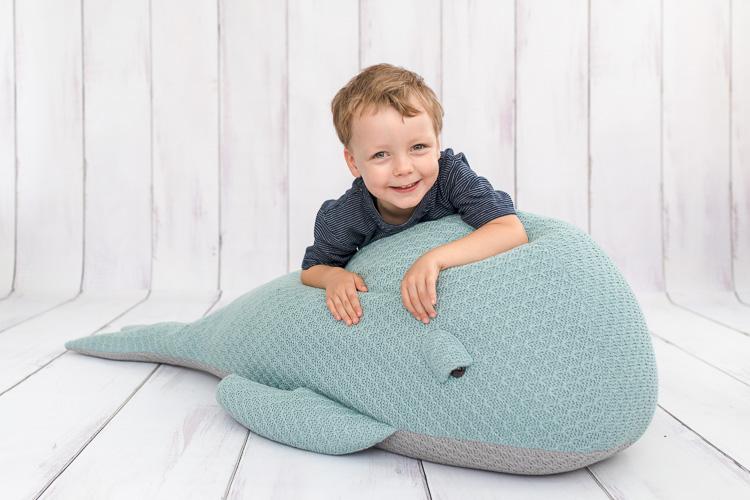 Junge liegt auf einen blauen Wal und lacht in die Kamera. Schulfotografie Ella Photography Essen