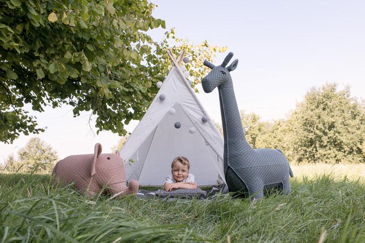 Junge liegt in einem weißen Zelt auf der Wiese, neben im steht ein rosa Elefant und eine graue Giraffe. Kindergartenfotografie Düsseldorf