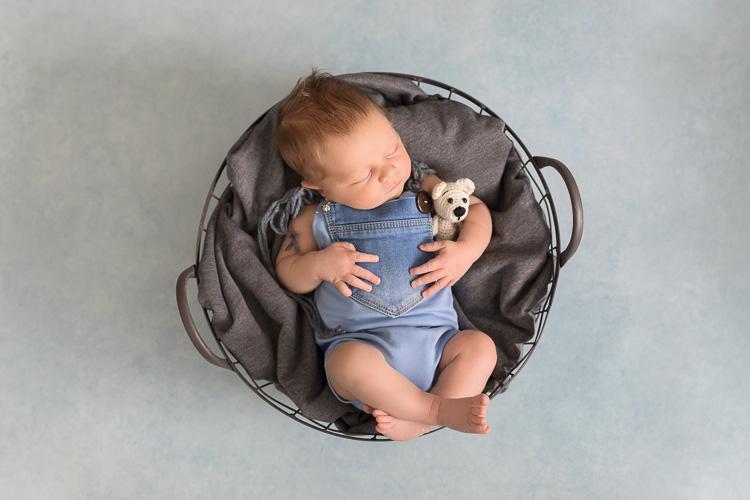 Neugeborenes liegt in einer Schale und schläft mit Teddy im Arm. Neugeborenenfotos von Ella Photography bei Duesseldorf.